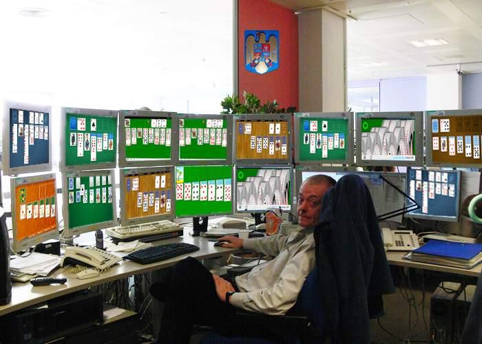 Un funcţionar se plânge că are colegii în concediu şi e nevoit să joace Solitaire pe 7 calculatoare!