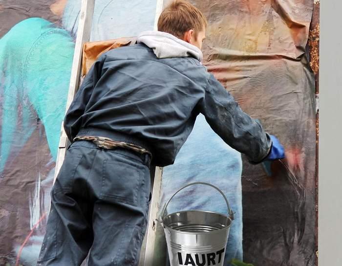 Muncă în zadar. Un român se chinuie să lipească afişe cu iaurt, că a auzit că ar conţine aracet