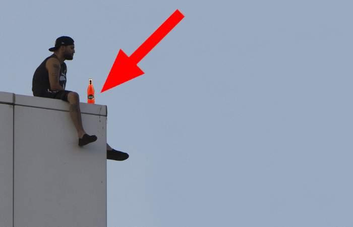 Un bărbat stă pe marginea unei clădiri cu un cidru în mână și amenință că îl bea