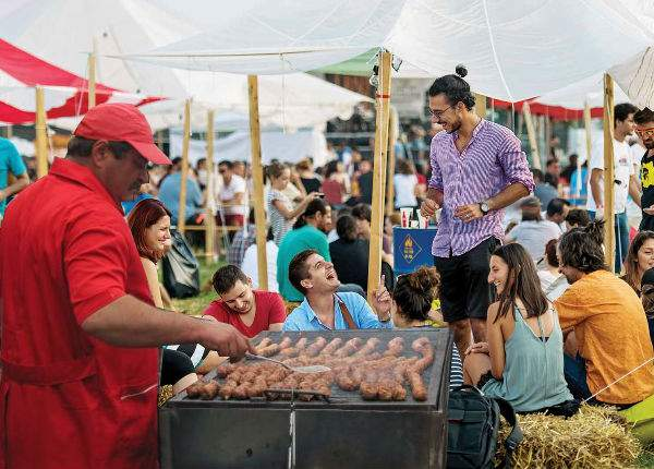 Toţi participanţii la un food truck festival din București, umiliţi la vânzări de taraba cu mici din parcare