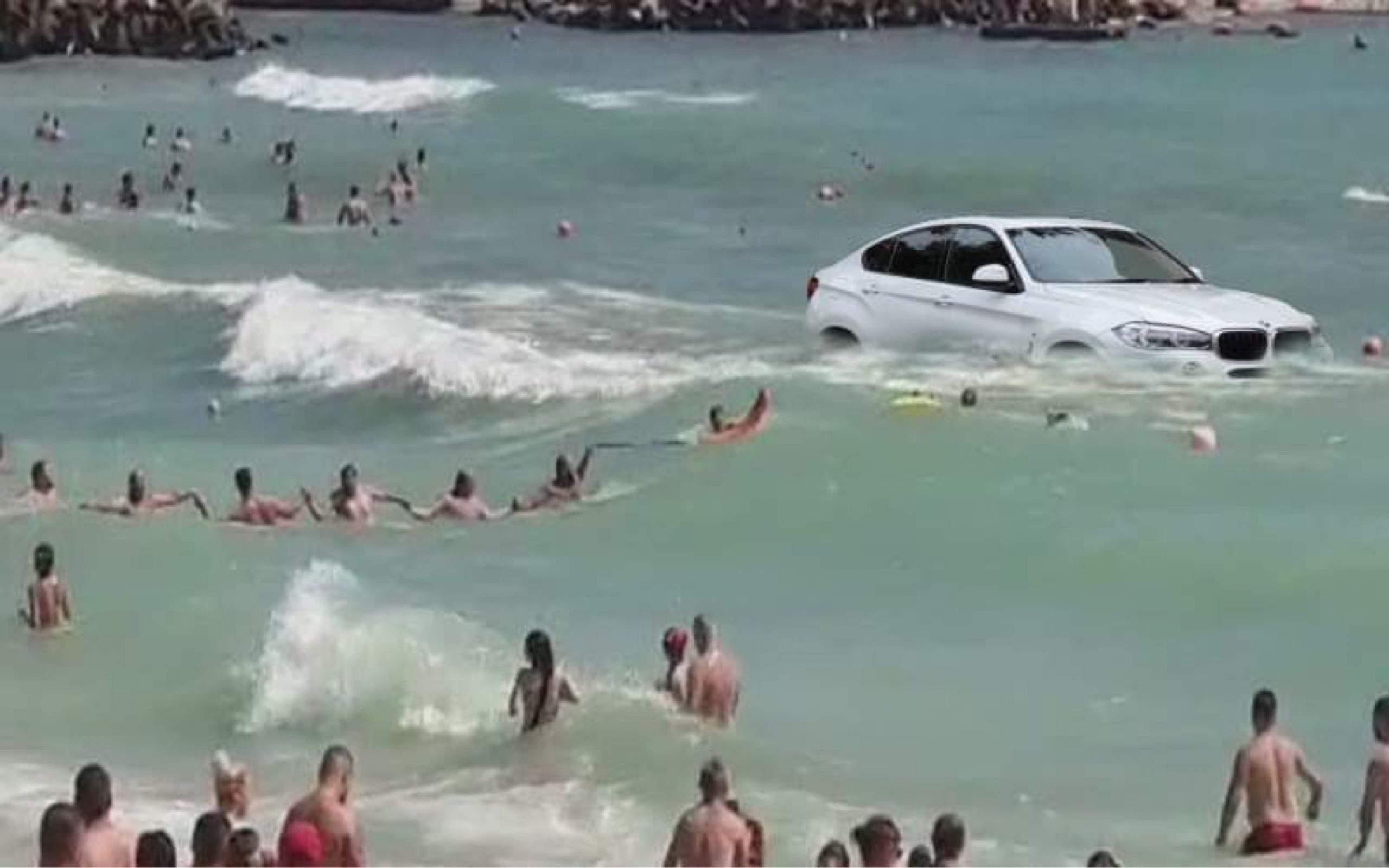 Emoționant. Lanț uman pe litoral pentru salvarea unui BMW din valuri
