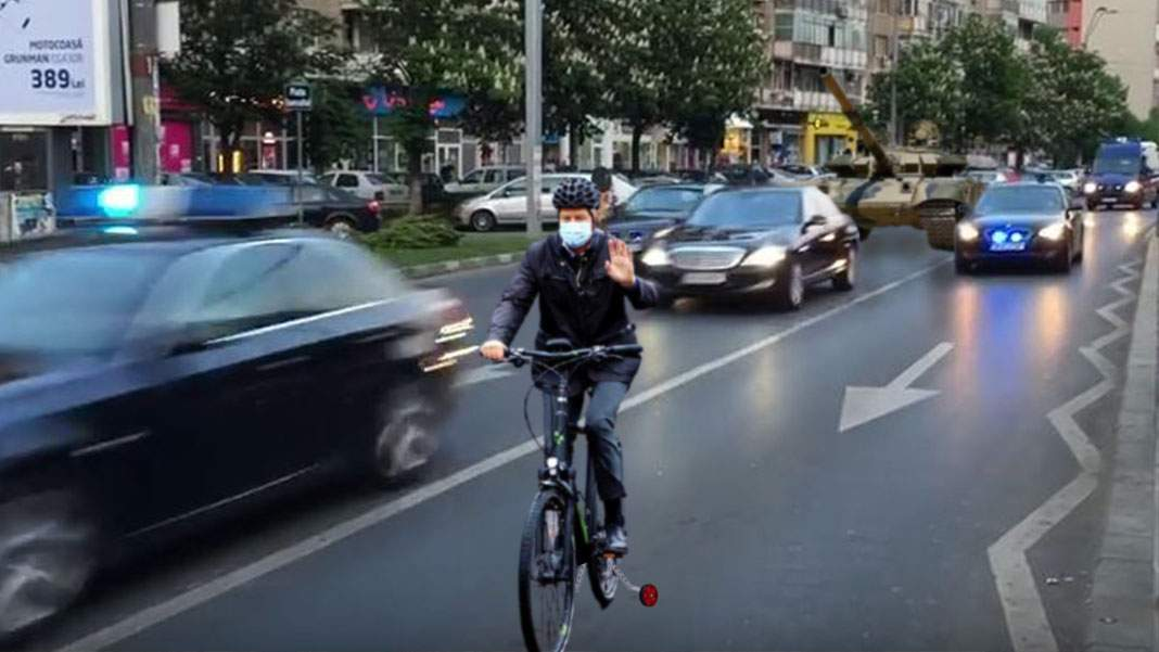 Iohannis, cu bicicleta la birou, urmat de coloana oficială de 18 maşini şi un tanc